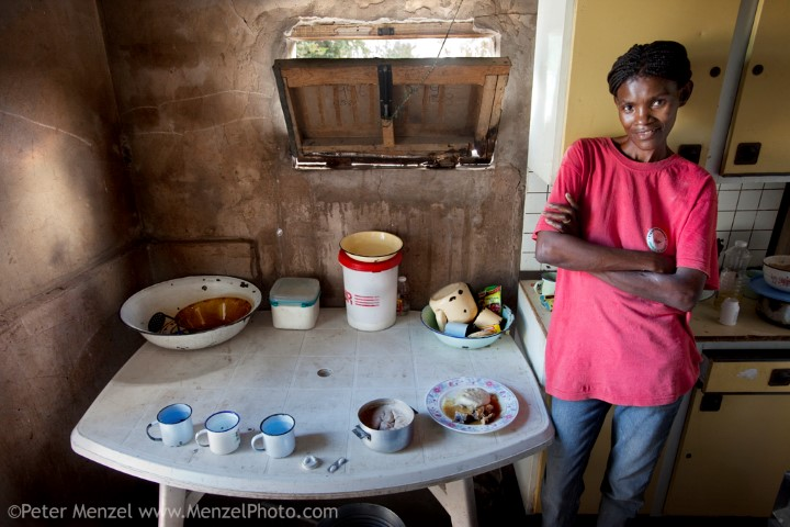 Marble Moahi, a mother living with HIV/AIDS, in the family kitchen in Kabakae Village, Ghanzi, Botswana with her typical day's worth of food and antiretroviral medications. (From the book What I Eat: Around the World in 80 Diets.) The caloric value of her day's worth of food on a typical day in March was 900 kcals. She is 32 years of age; 5 feet, 5 inches tall; and 92 pounds. Despite a decline in new HIV infections in sub-Saharan Africa, this region of the world remains the most heavily impacted by HIV/AIDS. MODEL RELEASED.