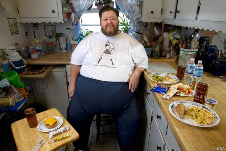 Rick Bumgardener with his recommended daily weight-loss diet at his home in Halls, Tennessee. (From the book What I Eat: Around the World in 80 Diets.) The caloric value of his day's worth of food in the month of February was 1,600 kcals. He is 54 years of age; 5 feet, 9 inches tall; and 468 pounds. Wheelchair-bound outside the house and suffering from a bad back and type 2 diabetes, he needs to lose 100 pounds to be eligible for weight-loss surgery. Rick tries to stick to the low-calorie diet pictured here but admits to lapses of willpower. Before an 18-year career driving a school bus, he delivered milk to stores and schools, and often traded with other delivery drivers for ice cream. School cafeteria staff would feed the charming Southerner at delivery stops, and he gained 100 pounds in one year. The prescription drug fen-phen helped him lose 100 pounds in seven months, but he gained it all back, plus more. MODEL RELEASED.