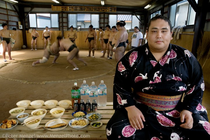 "Takeuchi Masato, a professional sumo wrestler whose ring name is Miyabiyama (meaning ""Graceful Mountain""), with his day's worth of food in the team's practice ring in Nagoya, Japan. (From the book What I Eat: Around the World in 80 Diets.) The caloric value of his typical day's worth of food in June was 3500 kcals. He is 29 years of age; 6 feet, 2 inches tall; and 400 pounds. Miyabiyama's stable runs through a brutal three-hour practice—sweaty, combative, and silent. Miyabiyama wears the white mawashi (at left) denoting his sekitori status during practice. His food may not look like much for a 400-pound man, but it's enough to maintain his weight and give him energy for the ring. When he isn't in intensive training before a match, he is wined and dined nightly by sponsors. The portrait above is a composite, taken on two consecutive days: the sumo association wouldn't allow Miyabiyama to be photographed during practice. Miyabiyama (His ring name—Masato Takeuchi is his given name), 29, a sumo wrestler with the Musashigawa Beya of Tokyo is that stable's (beya's) premier wrestler and is currently at the sekiwake (junior champion) level. He is one of the largest of the Japanese sumos and would probably have moved up even further in the ranks had he not suffered a severe shoulder injury. He is only just now returning to matches. Sumos cook and eat chanko nabe—a stew pot of vegetable and meat or fish at nearly every meal. It is eaten with copious amounts of rice and numerous side dishes. Miyabiyama eats now to maintain his weight rather than to gain it, unlike the younger less gargantuan wrestlers in his stable who are eating a lot to pack on weight. Although he is wined and dined by the sponsors of his team, during the period of these photographs he was training for the next matches in Nagoya, and therefore he wasn't eating out in restaurants nor drinking alcohol. MODEL RELEASED."