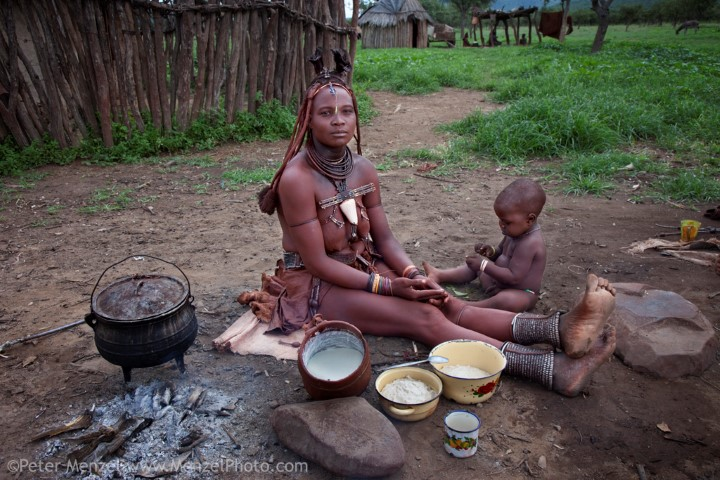 Viahondjera Musutua, a Himba tribeswoman, sits outside the house at her father's village with her youngest son and her typical day's worth of food. (From the book What I Eat: Around the World in 80 Diets.) The caloric value of her day's worth of food on a day in March was 1500 kcals. She is 23 years of age; 5 feet, 8 inches tall: and 160 pounds. The 23-year-old mother of three lives in a small village a seven-hour walk south from her father's village but visits yearly to collect her share of the family corn. Her traditional dress includes a full body glaze of otjize, a cosmetic made of ground ochre, butterfat, and plant resin. She wears a fertility necklace and other jewelry made with leather and metal beads, a goatskin leather skirt she made herself, and an erembe, the traditional Himba headdress of married women. The hairstyles and adornments of both men and women change according to their stage of life. Model Released.