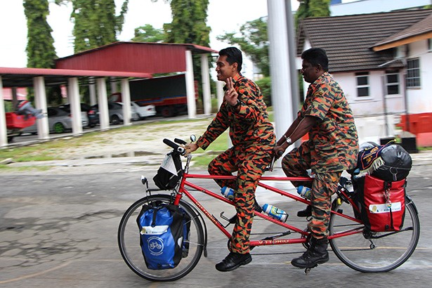 firemen trying out one of the tandems bicycles