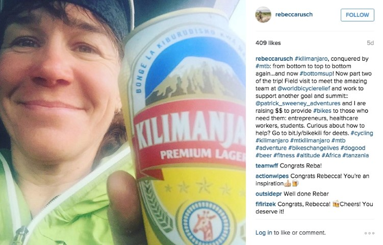 Rebecca Rusch with a summit beer on top of Kilimanjaro