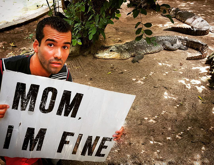 Jonathan Quiñonez Travels The World With Giant Mom Im Fine Sign - Guy photographs his girlfriend as they travel the world